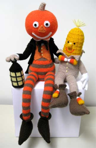 A photo of a knitted jack-o-lantern man and Maizey